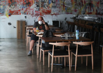 MIAMI, FLORIDA - JULY 10: Ryan Pines, who works at Buya restaurant, sits in the empty restaurant after it was was closed on July 10, 2020 in Miami, Florida. Mr. Pines wasn't sure what his next step will be after his job was eliminated due to the closure. Jeff Grosser, a co-owner, said they had to throw out about $8,000 worth of food and lay off 22 employees due to closure orders. Mr. Pines and other restaurant owners in Miami-Dade County say county Mayor Carlos Gimenezs decision to close restaurant dining halls amid the surge in COVID-19 cases is unfair to them as other businesses stay open. They claim there is no clear evidence that closing them is part of a realistic plan that will effectively manage the current crisis in the spread of COVID and they should be able to stay open.   Joe Raedle/Getty Images/AFP