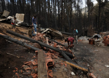 People clean rubble in Las Golondrinas town, in Chubut province, Argentina, on March 11, 2021, after a forest fire. - Seven people were injured and 15 more missing on Wednesday as forest fires ripped through Argentine Patagonia, official sources said. Some 200 people had to be evacuated and around 100 homes were damaged by fire in an area of forests and lakes popular with tourists close to the Andes mountain range. (Photo by FRM / AFP)
