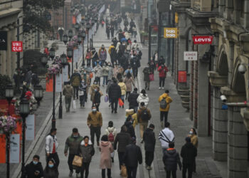 People walk along a pedestrian street in Wuhan, China's central Hubei province on January 23, 2021, one year after the city went into lockdown to curb the spread of the Covid-19 coronavirus. (Photo by Hector RETAMAL / AFP)