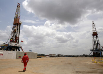 FILE PHOTO: An oilfield worker walks next to drilling rigs at an oil well operated by Venezuela's state oil company PDVSA, in the oil rich Orinoco belt, April 16, 2015.. REUTERS/Carlos Garcia Rawlins/File Photo
