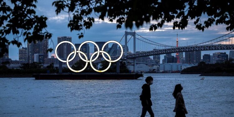 (FILES) This file photograph taken on April 28, 2021, shows a general view of the Olympic rings lit up at dusk on the Odaiba waterfront in Tokyo. - US drugs giant Pfizer and its German partner BioNTech on May 6, 2021, have announced a deal with the International Olympics Committee to provide vaccines to competitors and staff at the Tokyo games. In a statement, the firms said they would coordinate with national sporting bodies to make sure that coronavirus vaccines are available to anyone who needs one before travelling to Japan (Photo by CHARLY TRIBALLEAU / AFP)