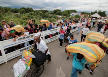 People cross the Simon Bolivar international bridge to Venezuela, on October 23, 2019 in Cucuta, Colombia, prior to its temporary closure by the Colombian authorities as a security measure for the upcoming October 27 regional elections. . - The bridge will reopen on October 27, soon after the election. (Photo by Schneyder MENDOZA / AFP)